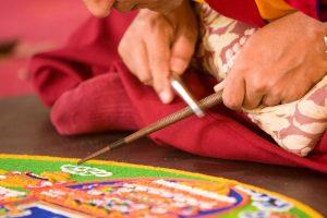 Mehrere Mönche arbeiten an einem Mandala. Quelle: Vladimir Melnik / Shutterstock.com